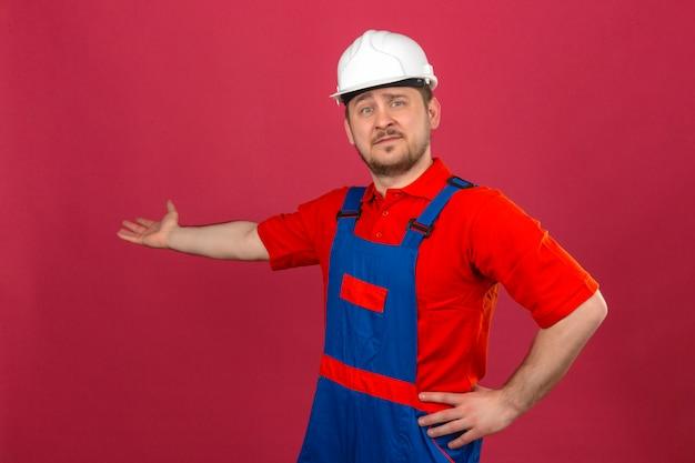 Uniforme da costruzione e casco di sicurezza d'uso dell'uomo del costruttore che indicano da parte con la palma aperta della mano che mostra a copia spazio sorridendo sicuro sopra la parete rosa isolata