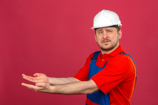 Builder man wearing construction uniform and security helmet pointing aside with hands open palms showing copy space smiling confident over isolated pink wall