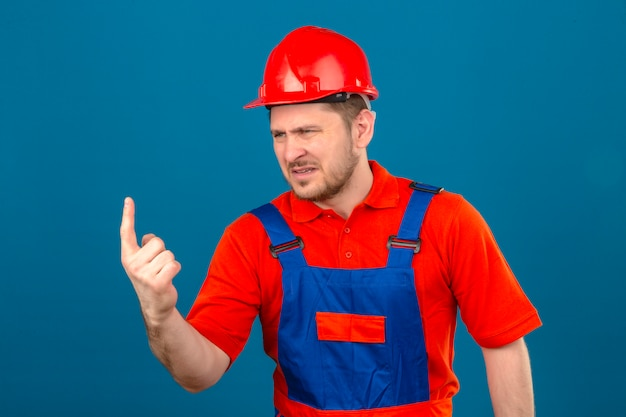 Builder man wearing construction uniform and security helmet pointing displeased and frustrated to the side standing over isolated blue wall