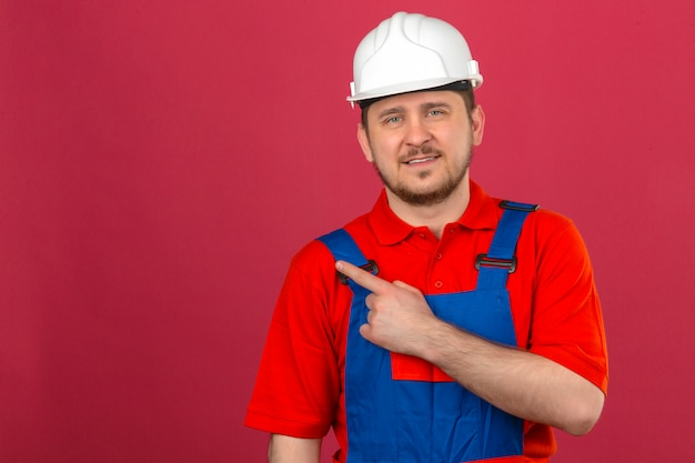 Uniforme da costruzione dell'uomo del costruttore e casco di sicurezza che indicano dito per copiare spazio che sembra sicuro che controlla parete rosa isolata