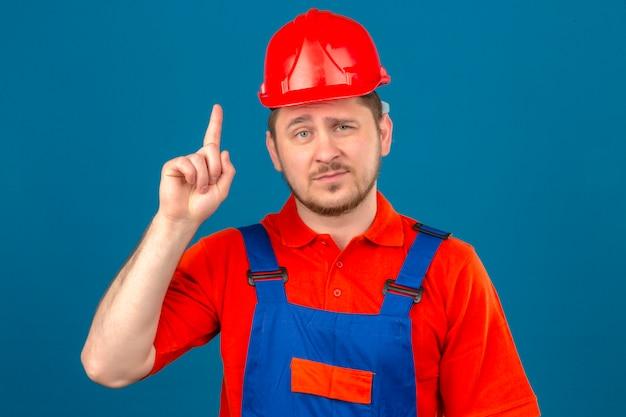 Uniforme da costruzione dell'uomo del costruttore e casco di sicurezza che indicano dito su che sorride sicuro che ha grande idea sopra la parete blu isolata