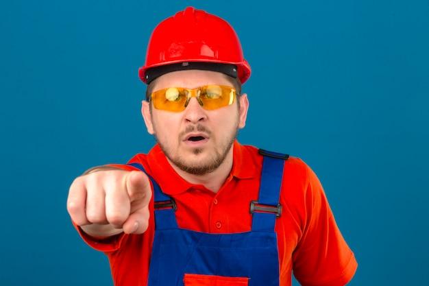 L'uniforme d'uso della costruzione dell'uomo e il casco di sicurezza colpiti indicano con il dito la macchina fotografica sopra la parete blu isolata