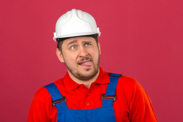 Builder man wearing construction uniform and security helmet showing grimace face crossing his eyes sticking out tongue over isolated pink wall