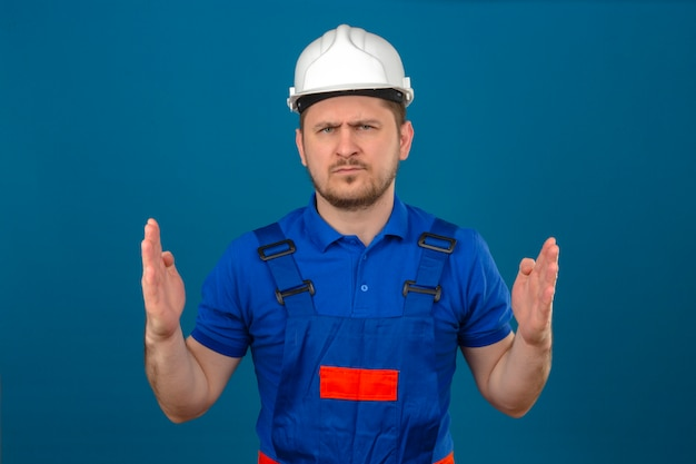 Builder man wearing construction uniform and security helmet showing large size sign with frowning face measure symbol standing over isolated blue wall