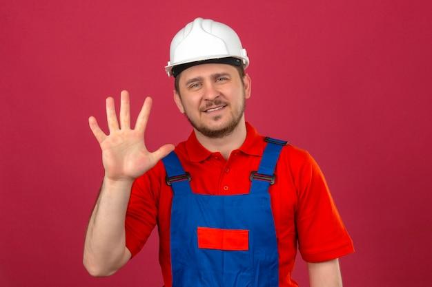 Uniforme edile da portare dell'uomo del costruttore e casco di sicurezza che mostrano e che indicano su con le dita numero cinque che sorridono sicuro sopra la parete rosa isolata