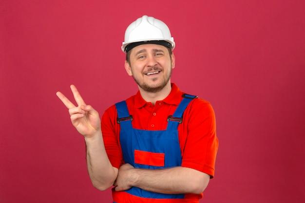 Uniforme da costruzione dell'uomo del costruttore e casco di sicurezza che mostrano e che indicano su con le dita numero due o il segno di vittoria che sorridono allegramente sopra la parete rosa isolata