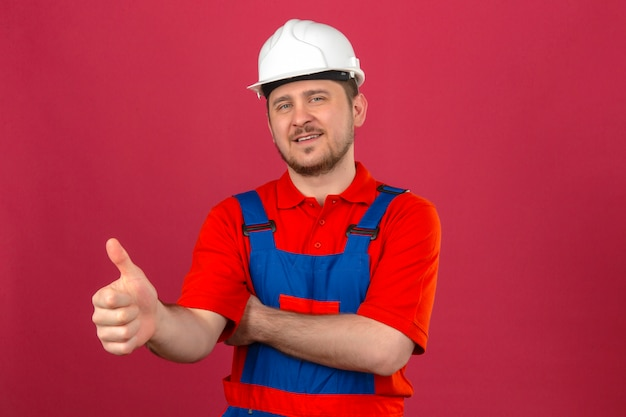 Builder man wearing construction uniform and security helmet smiling friendly showing thumb up standing over isolated pink wall