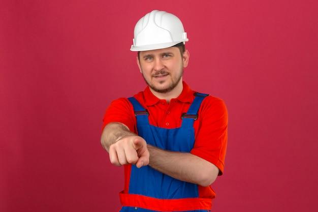 Uniforme da costruzione dell'uomo del costruttore e casco di sicurezza che sorridono e che esaminano la macchina fotografica che indica con il dito la macchina fotografica che controlla parete rosa isolata