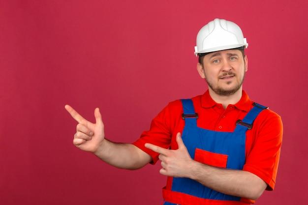 Uomo del costruttore che indossa l'uniforme di costruzione e casco di sicurezza che sorride e che esamina la macchina fotografica che indica con due mani e dita al lato che sta sopra la parete rosa isolata