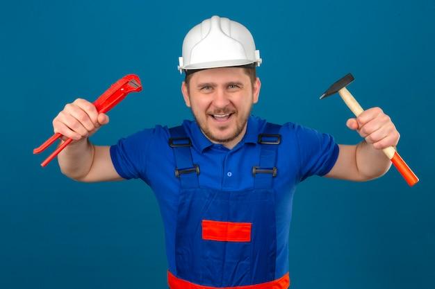 Uomo del costruttore che indossa l'uniforme di costruzione e casco di sicurezza in piedi con le mani sollevate tenendo il martello e la chiave regolabile in posa minacciosa divertendosi sul muro blu isolato