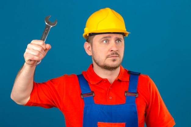 Uniforme da costruzione e casco di sicurezza d'uso dell'uomo del costruttore che minacciano di colpire con la chiave che guarda seriamente sopra la parete arancio isolata