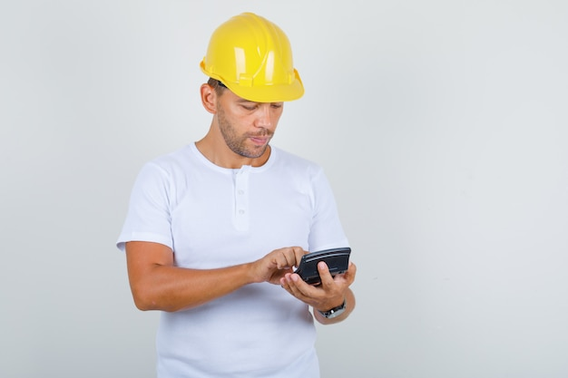 Builder man in white t-shirt, helmet using calculator and looking busy, front view.