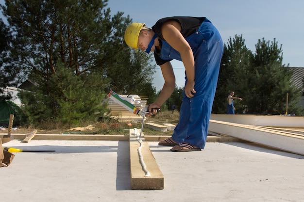 Строитель или плотник наносит клей на деревянную балку на строительной площадке из клеевого пистолета
