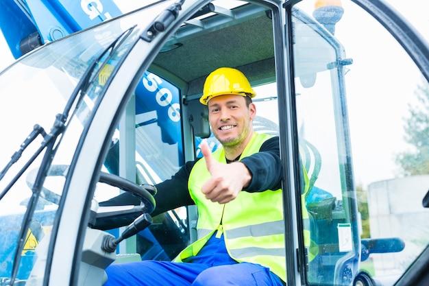 Строитель или водитель, управляющий экскаватором на строительстве или строительной площадке