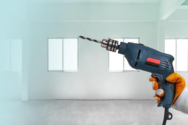 Строитель или рабочий сверля с машиной или сверлом
