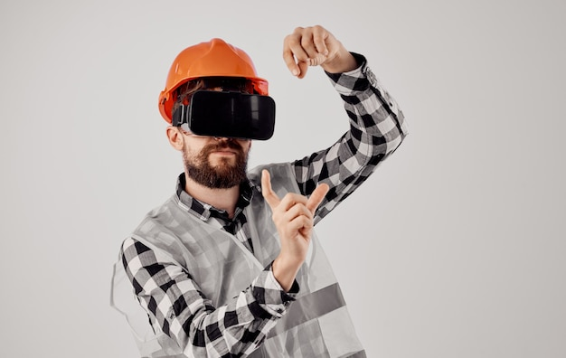 A builder in an orange helmet and 3d glasses gestures with his hands copy space light space