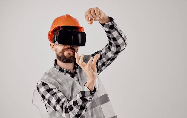 A builder in an orange helmet and 3d glasses gestures with his hands light.