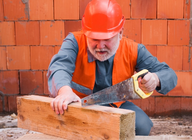 Builder in protective helmet cutting wood board with saw. professional construction worker carpenter in hard hat.
