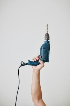 Строитель, поднимающий электродрель