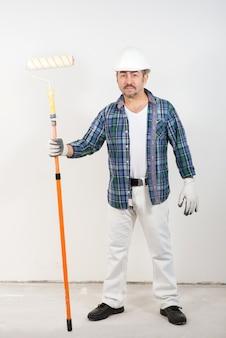 흰 벽에 그의 손에 긴 페인트 롤러를 들고 작성기 수리공