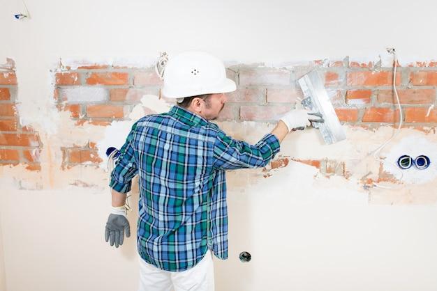 집 수리 중 퍼티 나이프로 벽돌 벽을 석고 보호 헬멧에 작성기 수리공