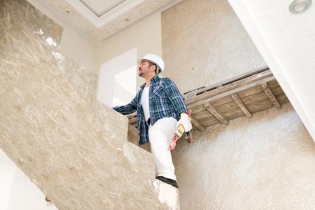 작성기, 건설 중 콘크리트 계단에 도구로 보호 헬멧 수리공