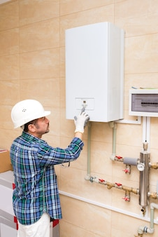 Строитель-ремонтник-сантехник включает водонагреватель автономного отопления в доме