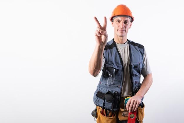 Строитель показывает знак козы в рабочей одежде и каске на светло-сером фоне