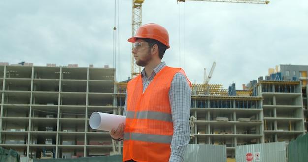 Строитель, стоящий перед строящимся зданием