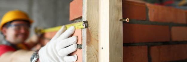 レンガの壁に巻尺を取るビルダーをクローズアップ