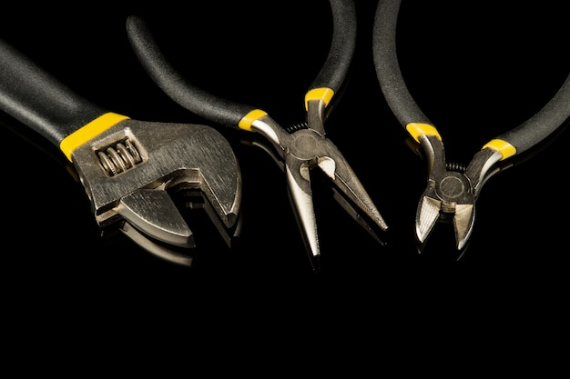 Инструменты строителя на черном изолированном фоне, подготовленные профессиональным мастером перед ремонтом или строительством