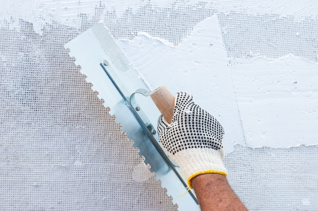 Builder using plastering tool for finishing wall and floor.