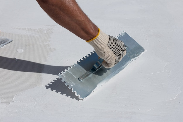 Builder using plastering tool for finishing wall.