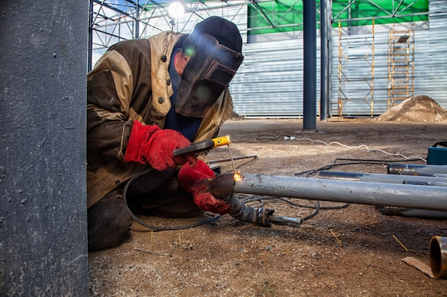 A builder welder in brown working clothes welds a metal product with arc