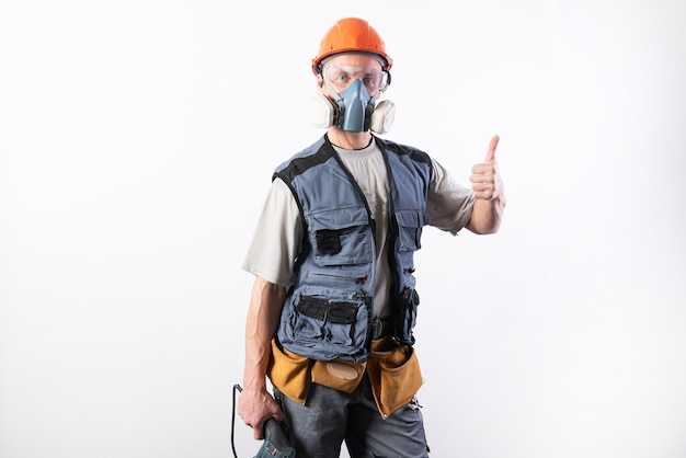 ヘルメットにドリルパンチャーと呼吸器を備えたビルダー。親指を立てる目的を問わず。
