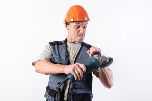 헬멧에 앵글 그라인더가 있는 빌더, 그의 얼굴에 재미있는 표정이 있습니다. 어떤 목적을 위해.