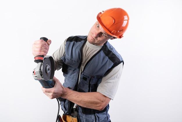 그의 얼굴에 재미 있는 표정으로 헬멧에 앵글 그라인더와 빌더. 어떤 목적을 위해.
