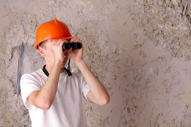 Builder with binoculars at the of the gray plastered walls