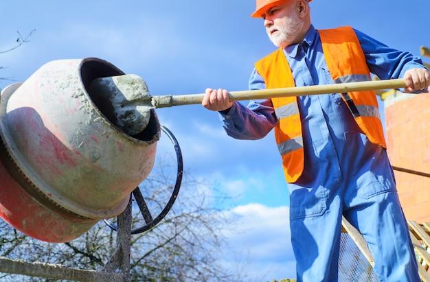 Строитель с бетономешалкой готовит цементный раствор. рабочий-строитель с лопатой в руке.