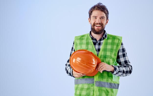 손에 오렌지 하드 모자와 반사 조끼 푸른 공간 복사 공간 작성기