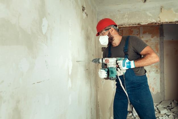 Строитель с перфоратором сверлит отверстия в бетонной стене