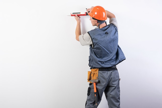 Builder with sealant. in work clothes and hard hat. on a light gray background. for any purpose.
