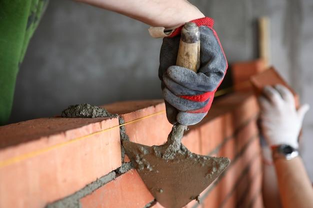 Строитель с помощью шпателя для удаления избытка цемента