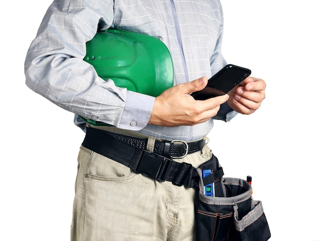 Builder with tools and hard hat holds smartphone in his hands