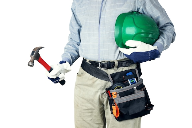 Builder with tools holds hammer and hard hat, helmet in his hands