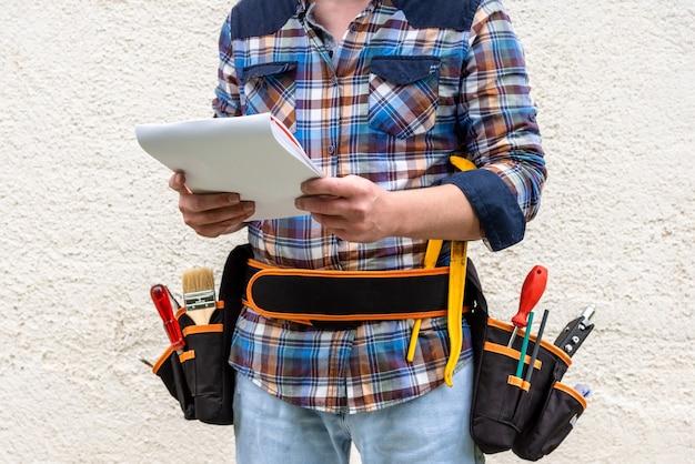 彼のベルトにツールを持つビルダー