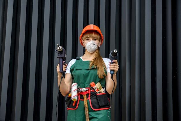 ツールを備えたビルダー。緑のつなぎと抽象的な背景にドリルマシンを保持している保護マスクの女性
