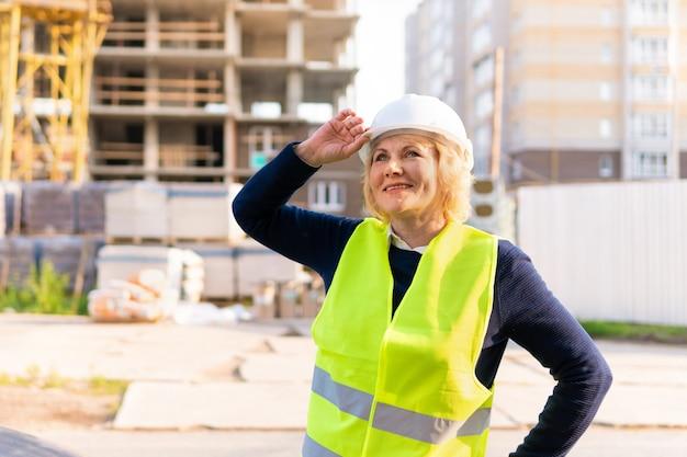 緑のベストと白いヘルメットの建設現場でビルダーの女性。彼女は微笑みます。