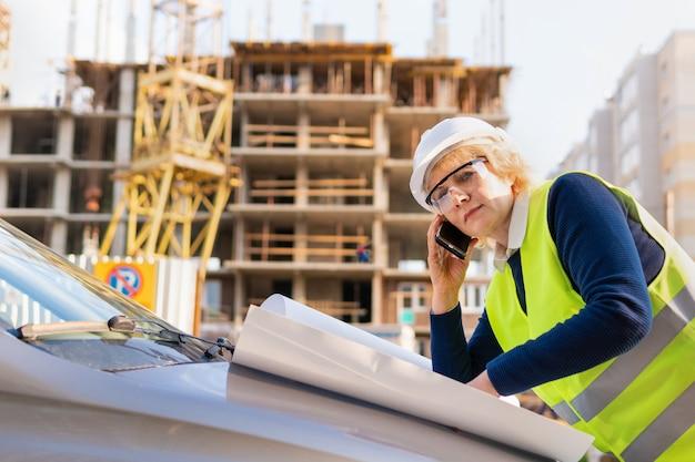 緑のベストと白いヘルメットの建設現場でビルダーの女性。彼女は電話で話します。