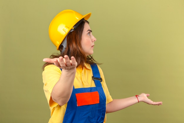 Builder woman in construction uniform and safety helmet looking aside shrugging shoulders spreading hands not understanding what happened clueless and confused expression over isolated green backg